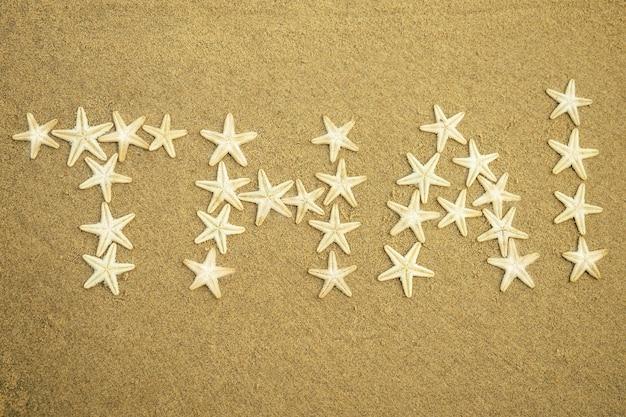 모래에 태국이라는 단어의 흰색 불가사리 비문. 바다의 별에서 모래에 태국입니다. 휴가 및 여행의 개념입니다.