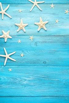 Белые морские звезды разных видов на голубом фоне. скопируйте пространство. вертикальный вид.
