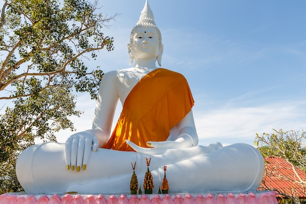 White statue of buddha sitting in the lotus position