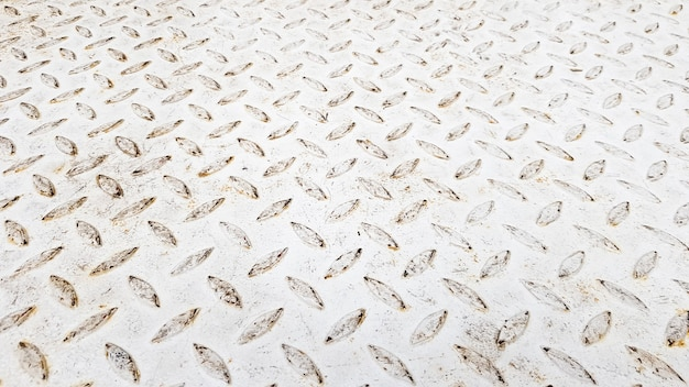 바닥 및 산업용 건물에 사용되는 엠보싱 다이아몬드 패턴의 흰색 강판. 배경으로 유용한 흰색 빈티지 강판입니다.