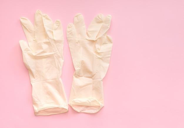 Белые стерильные медицинские хирургические резиновые перчатки для врача на розовом