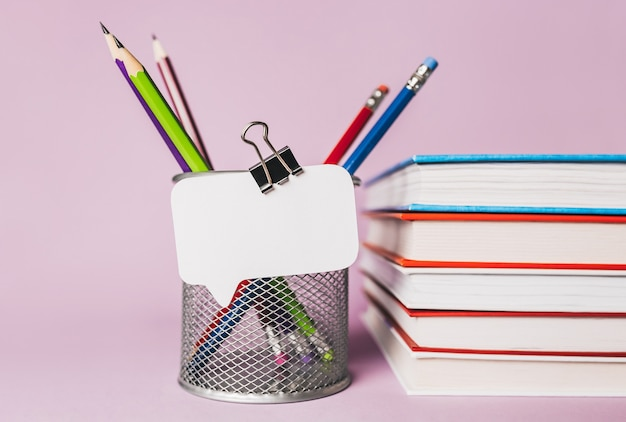 White sticker, books, notepad and pensil on workplace. mock up in copy space office purple background. it is important not to forget the note