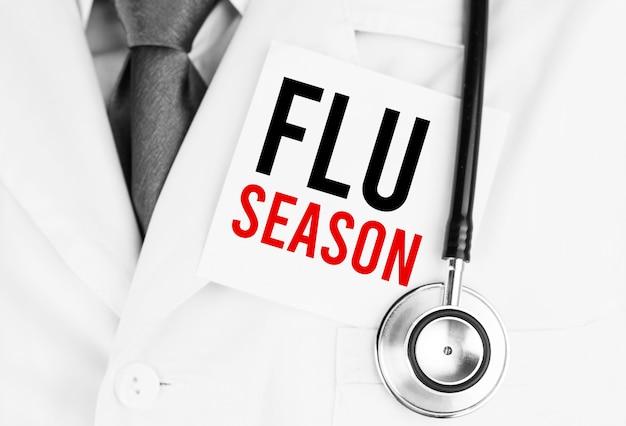 Белая наклейка с текстом сезона гриппа, лежа на медицинском халате со стетоскопом