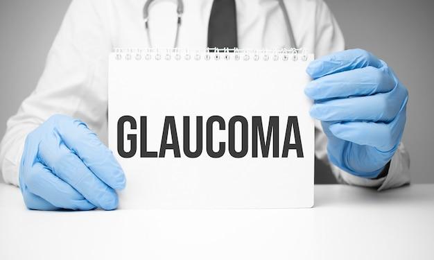 Белая наклейка с текстом глаукома в руках врача со стетоскопом