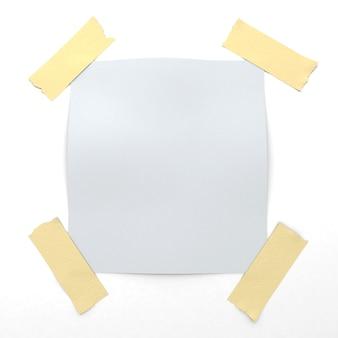 Белый стикер прикреплен к стене липкой лентой
