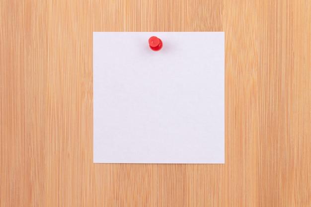 나무 메시지 보드에 고정된 흰색 스티커 메모