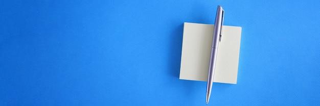 연한 파란색 배경에 펜이 있는 흰색 스티커 메모