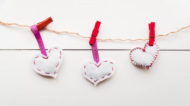 Cuori bianchi del punto sulla corda legata con le mollette da bucato rosse su corda contro la plancia di legno