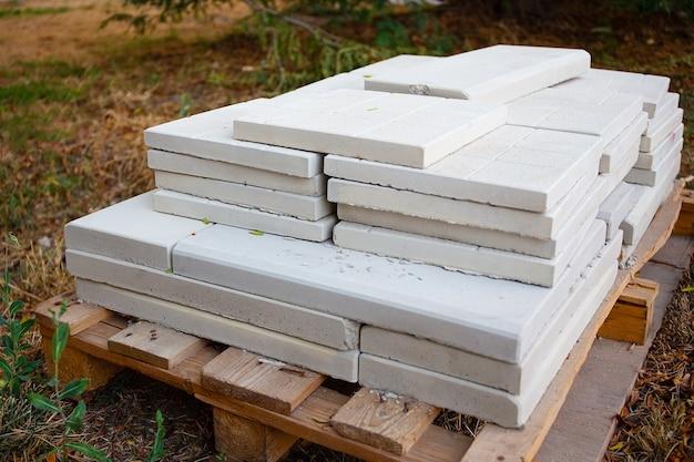 보행자 보도를 포장하기 위해 쌓인 흰색 돌 포장 석판, 건축 자재의 근접 촬영. 보도용 타일 더미. 건설 작업, 조경.