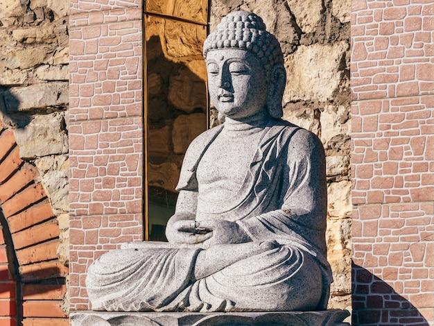 White stone statue of a buddha on masonry background
