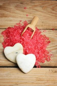 お風呂のための赤い塩の丘の上のハートの形の白い石、スパサロンでのロマンス