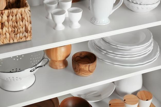 Белая подставка для хранения с посудой на кухне