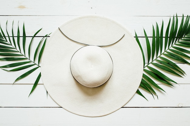 White straw hat and green palm leaves on wooden background