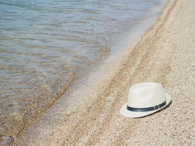 A white straw hat lies on the sand by the water sea beach on a summer sunny day sea vacation concept copy space