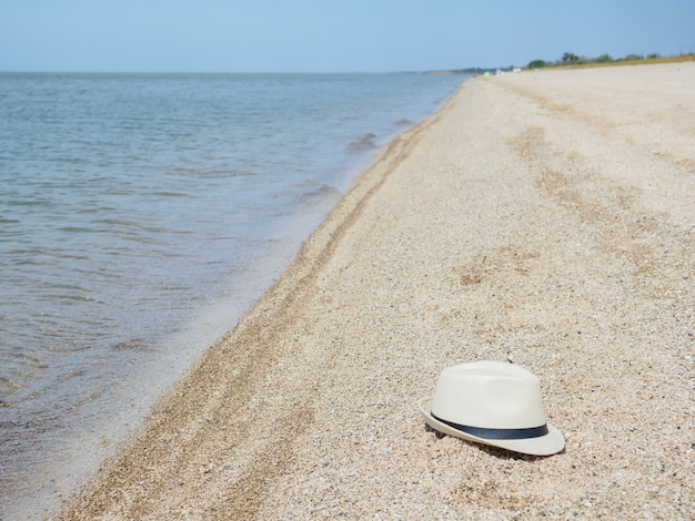 White straw hat lies on the sea beach near the water on a summer sunny day