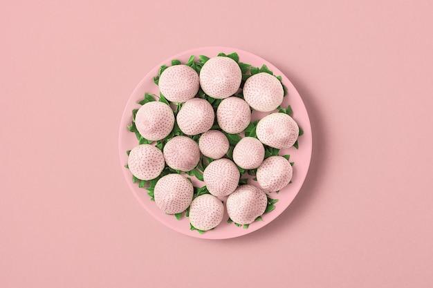 Белая клубника в тарелке на светло-розовом фоне. вид сверху.