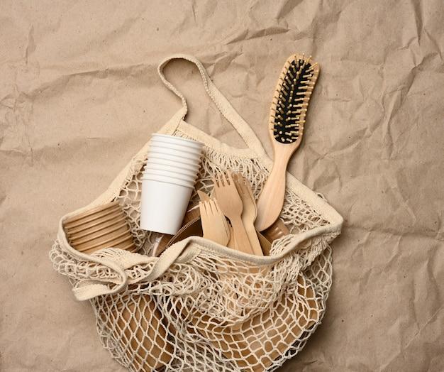 Белая авоська с одноразовой бумажной посудой и деревянными вилками на коричневой крафт-бумаге, вид сверху, без отходов