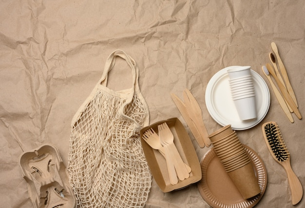 White string bag with disposable paper dishes and wooden forks on brown kraft paper, top view, zero waste