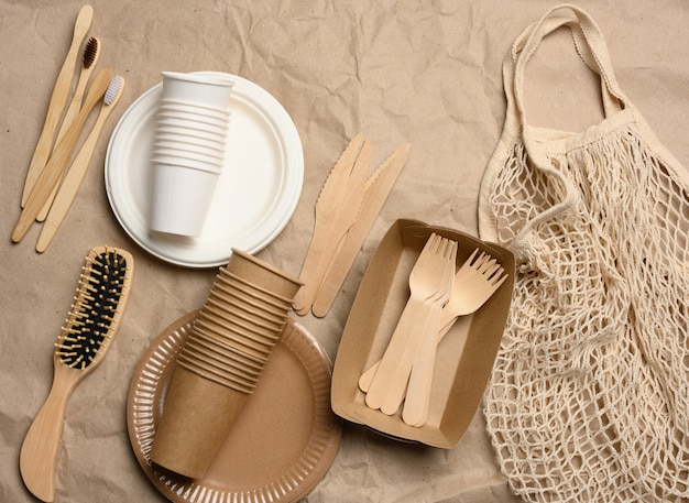 White string bag with disposable paper dishes and wooden forks on brown kraft paper, top view