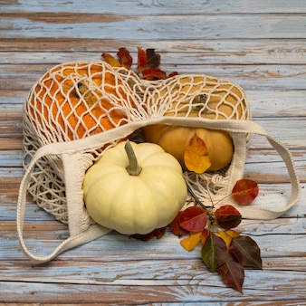 White string bag with pumpkins on an aged wooden table.