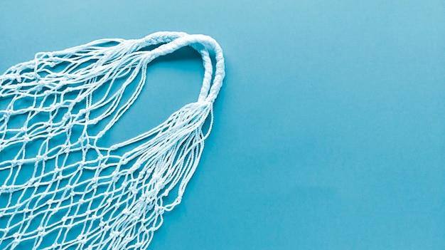 青色の背景に白い糸コットンエコバッグ。モノクロのシンプルなフラットレイアウトコピースペース。生態学ゼロ廃棄物の概念。