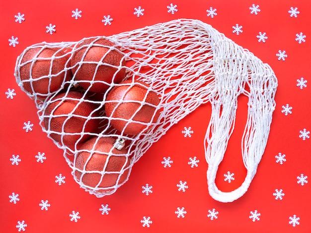 クリスマスツリーのボールが入った白いストリングコットンエコバッグ Premium写真