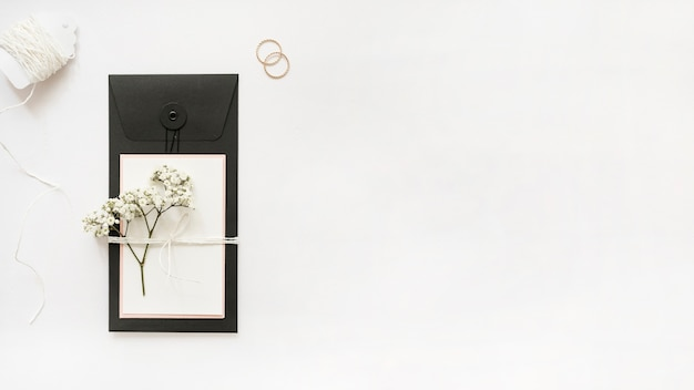 White strings; wedding rings and greeting card with baby's-breath flowers on white background