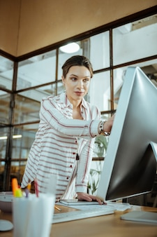 Блузка в белую полоску. красивая стильная женщина в белой полосатой блузке, усердно работающая в офисе