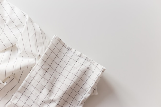 White striped and checkered tablecloth close-up, isolated on white with copy space.