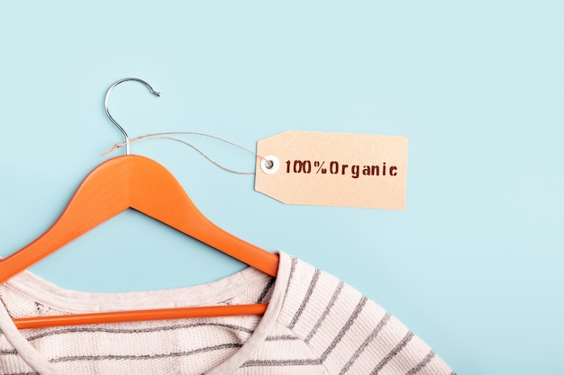 White striped sweatshirt on a hanger and tag with inscription 100% organic