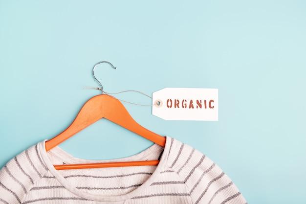 옷걸이에 흰색 줄무늬 스웨트셔츠와 유기농이라는 문구가 새겨진 태그. 친환경 의류