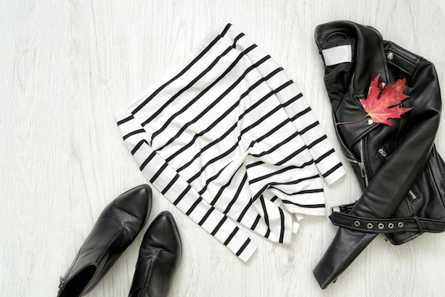 白のストライプのトップ、黒のジャケットと靴