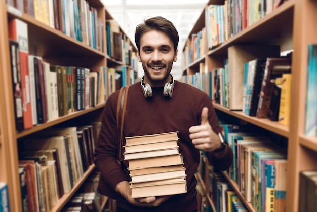 White student in sweater with books in aisle of library.