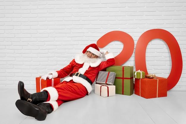 White studio with santa claus lying on floor among presents