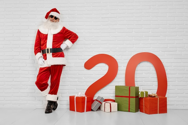 White studio with santa claus in sunglasses leaning on wall