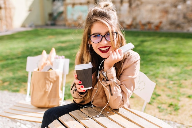 White stylish girl in big glasses drinks coffee in the park and listens to music in headphones with interest looking into the camera. coffee break in the outdoor cafe after shopping.