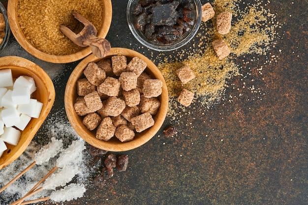 Белый сахар, кубики тростникового сахара, карамель в бамбуковой миске на темно-коричневом фоне бетонного стола. ассорти из разных видов сахара. вид сверху или плоская планировка.