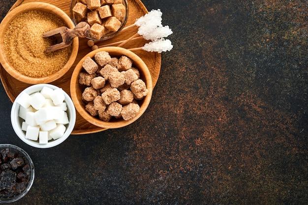 Белый сахар, кубики тростникового сахара, карамель в бамбуковой миске на темно-коричневом столовом бетоне