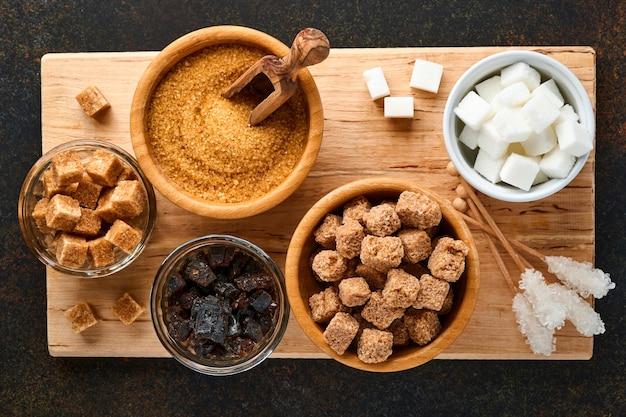 Белый сахар, кубики тростникового сахара, карамель в бамбуковой миске на темно-коричневом столе