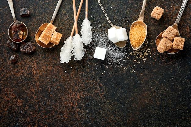Белый сахар, кубики тростникового сахара, карамель в чайных ложках на темно-коричневом столовом бетоне