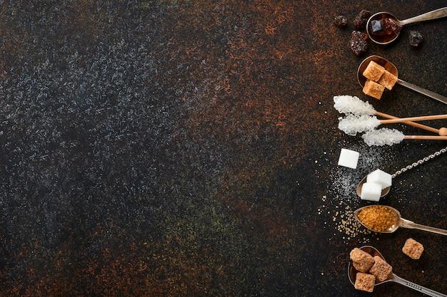 Белый сахар, кубики тростникового сахара, карамель в чайных ложках на темно-коричневом столе