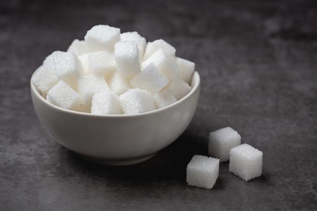 Cubi dello zucchero bianco in ciotola sulla tavola.