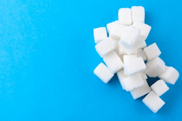White sugar cubes on a bright blue background