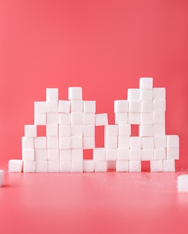 White sugar cubes composition on red