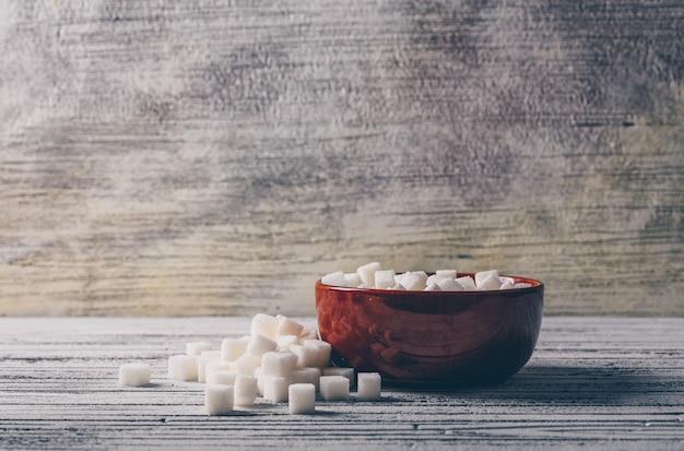 白い木製のテーブルの上にボウルに白い砂糖の立方体。側面図。