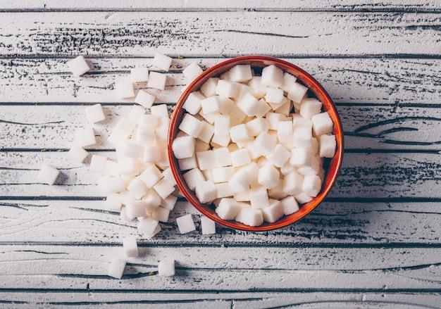 白い木製のテーブルの上にボウルに白い砂糖の立方体。上面図。