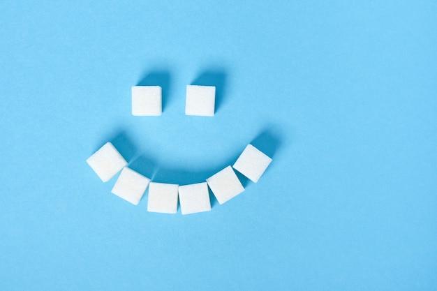 Кубики белого сахара выложены в виде грустной улыбки на синей поверхности крупным планом