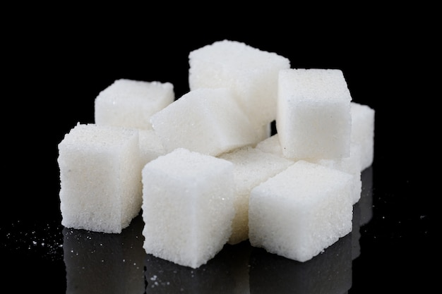 Кубики белого сахара на черной поверхности