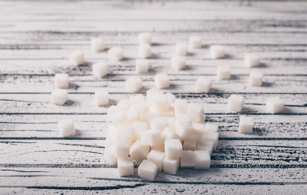 White sugar cubes on a white wooden table. high angle view.