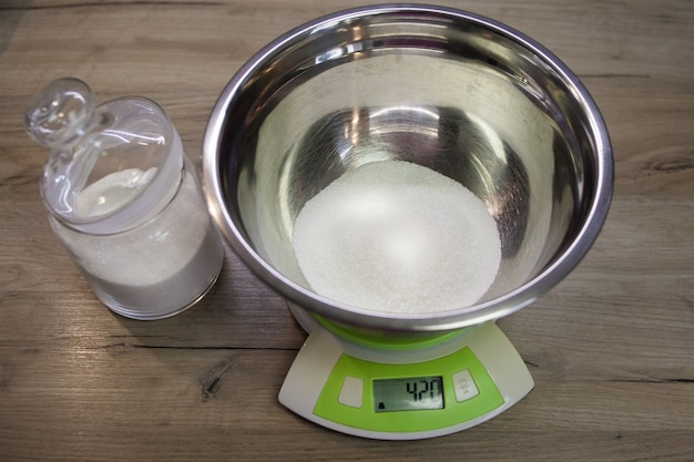 Белый сахар в миске на весах